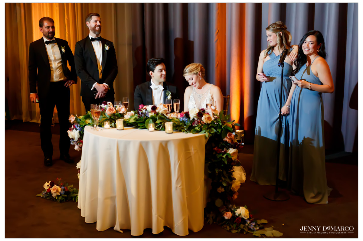 bridesmaids giving toasts to the bride and groom at their sweetheart table