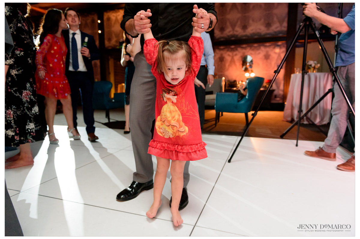 little girl in a princess dress dancing at the reception