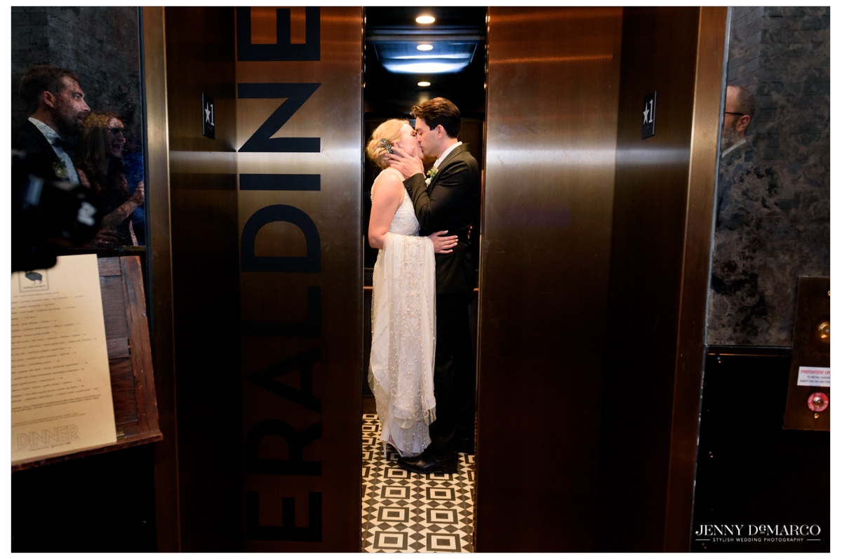 bride and groom kissing in the elevator as the doors close