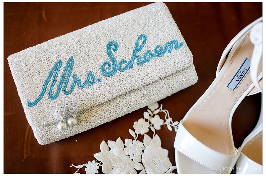 The bride's heals and purse with her new last name printed on them.