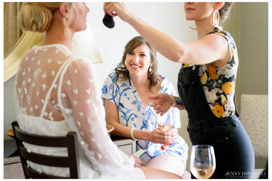 A friend of the bride watching as the bride gets the finishing touches of her makeup.