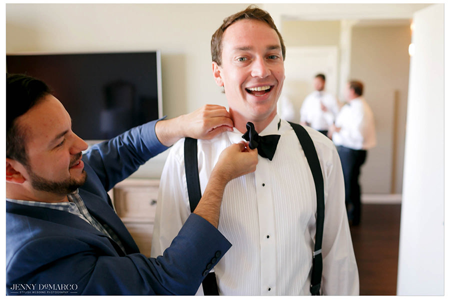 The groom gets his bow-tie adjusted in his hotel room before the ceremony.