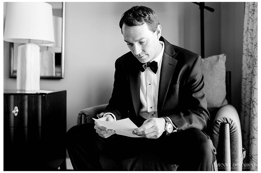 The groom reads a note before the ceremony in his hotel room.