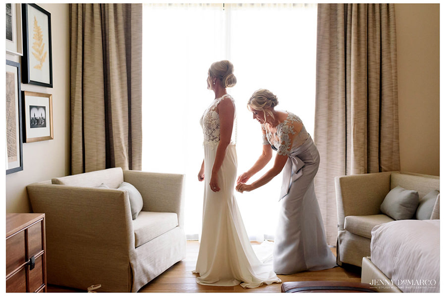 The bride gets her dress zipped up by her mother as she waits in her hotel room.