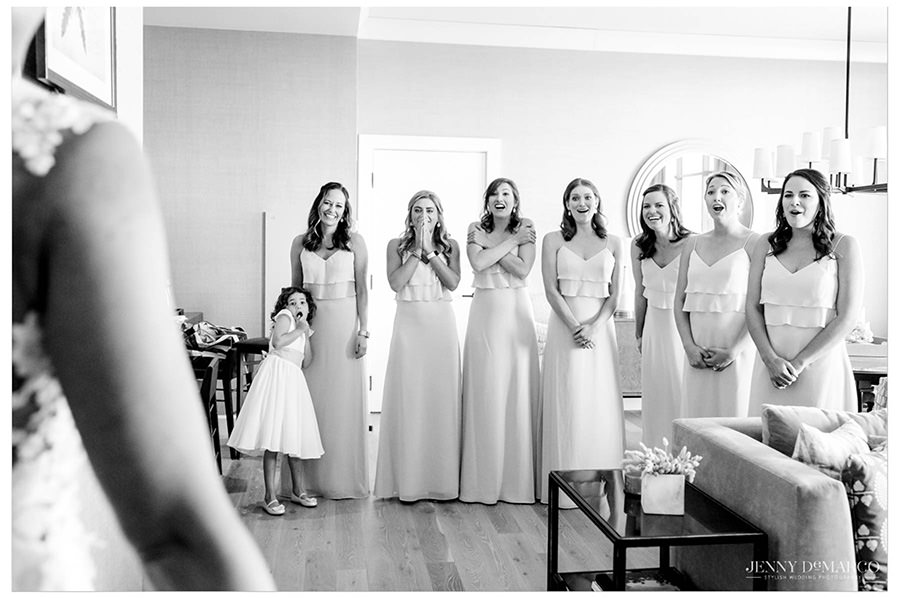 Bridesmaids express excitement as they see the bride for the first time on her wedding day.