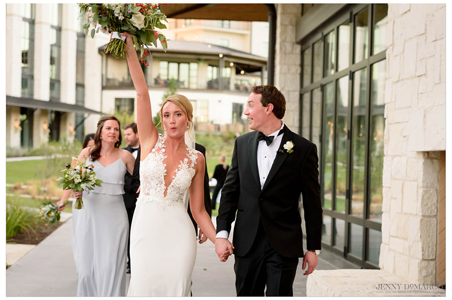 Bride cheers as she walks away with her husband.