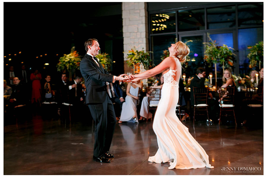 Bride laughs on the dance floor with her groom.