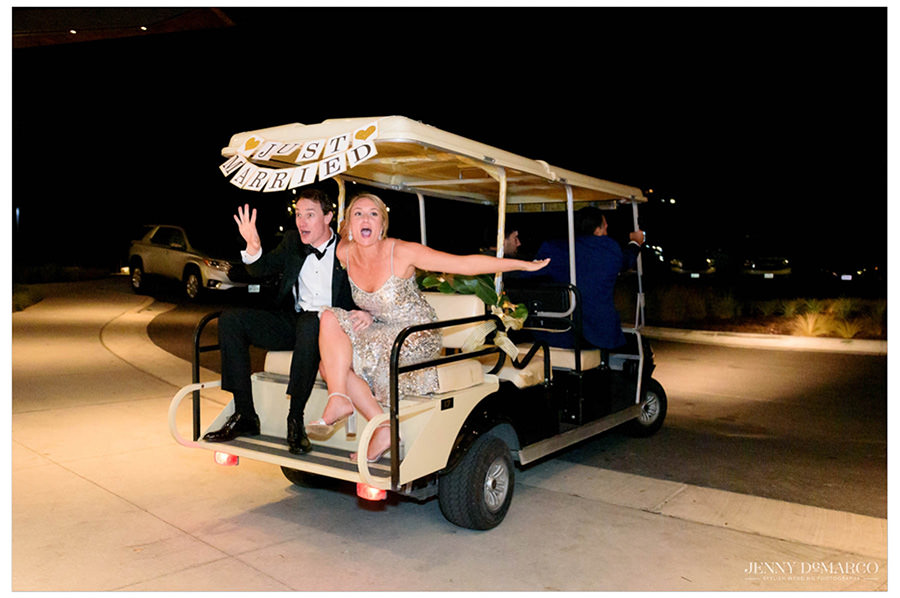 Bride and groom waving goodbye as they ride away on the golf cart.