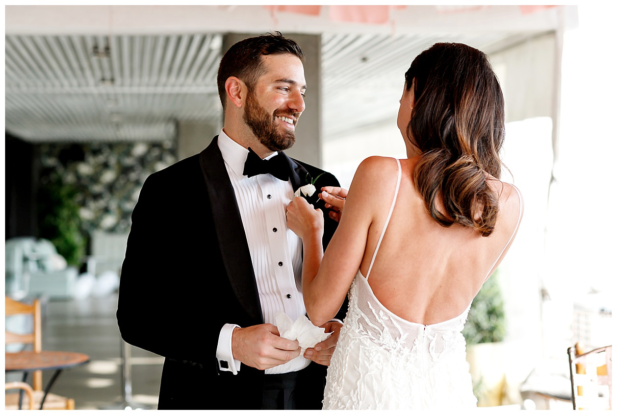 bride pinning on grooms boutonniere