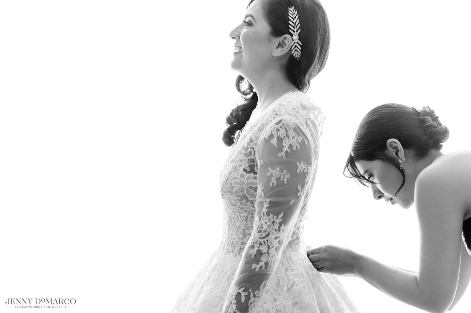 bridesmaid helping bride zip up her lace wedding dress