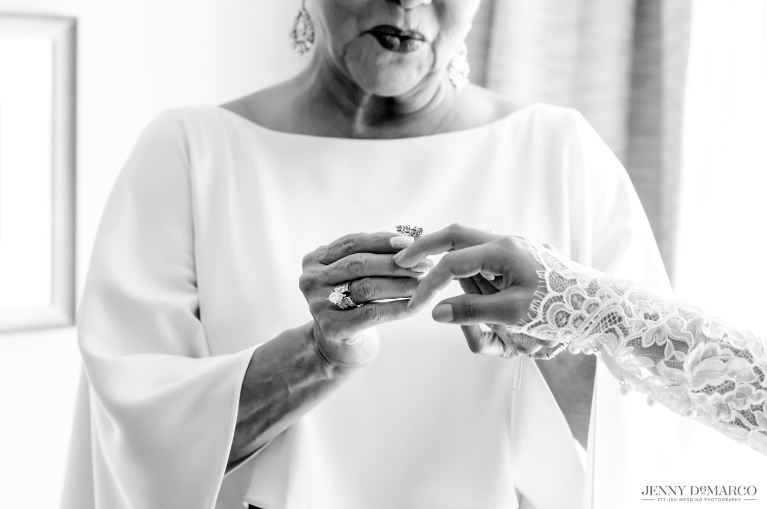 mother of the bride putting on the bride's gorgeous engagement ring for her