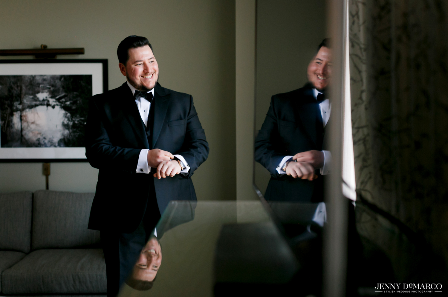 Groom putting on his cufflinks in the mirror