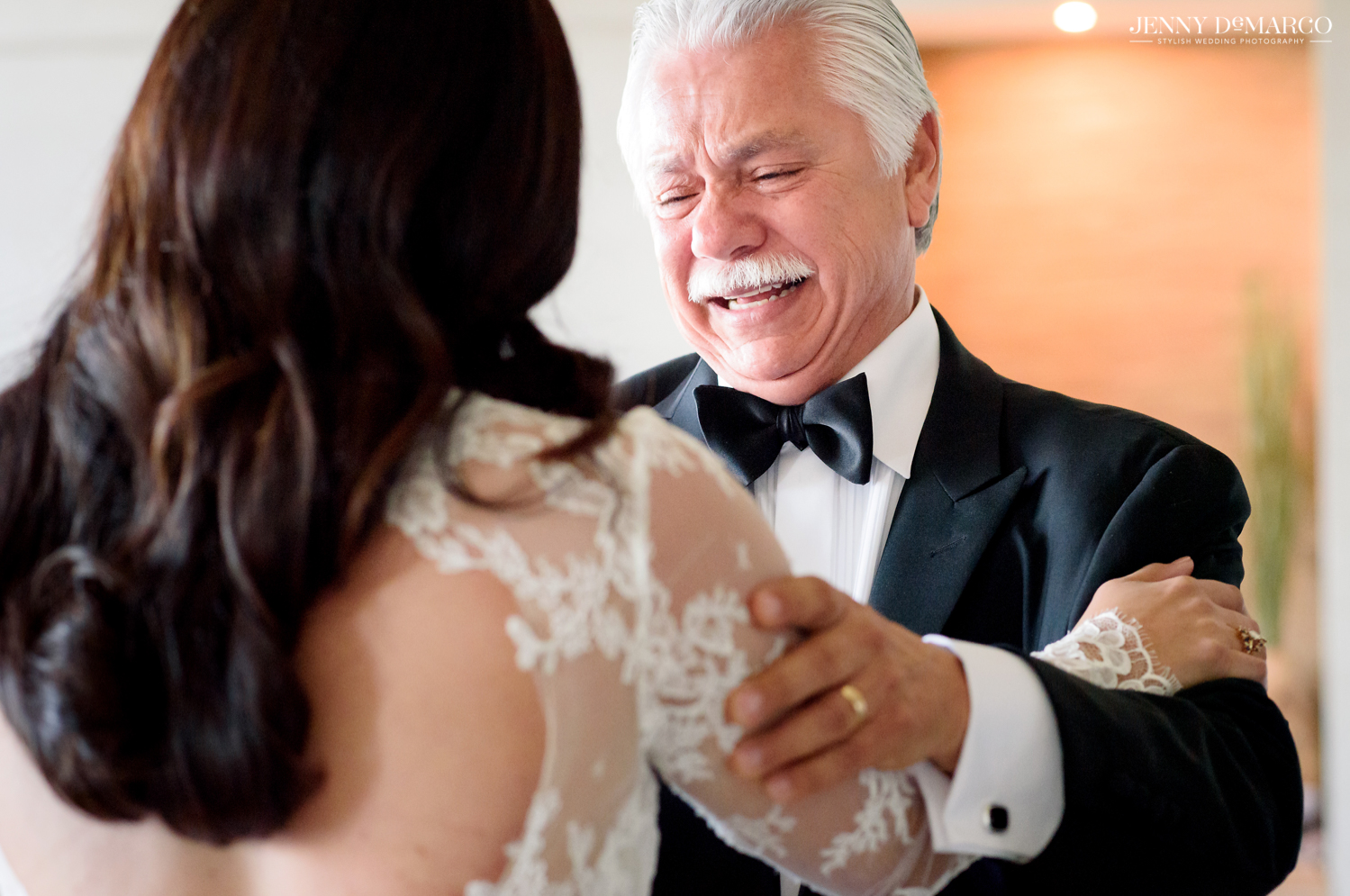 father of the bride crying while he looks at his daughter in her wedding dress