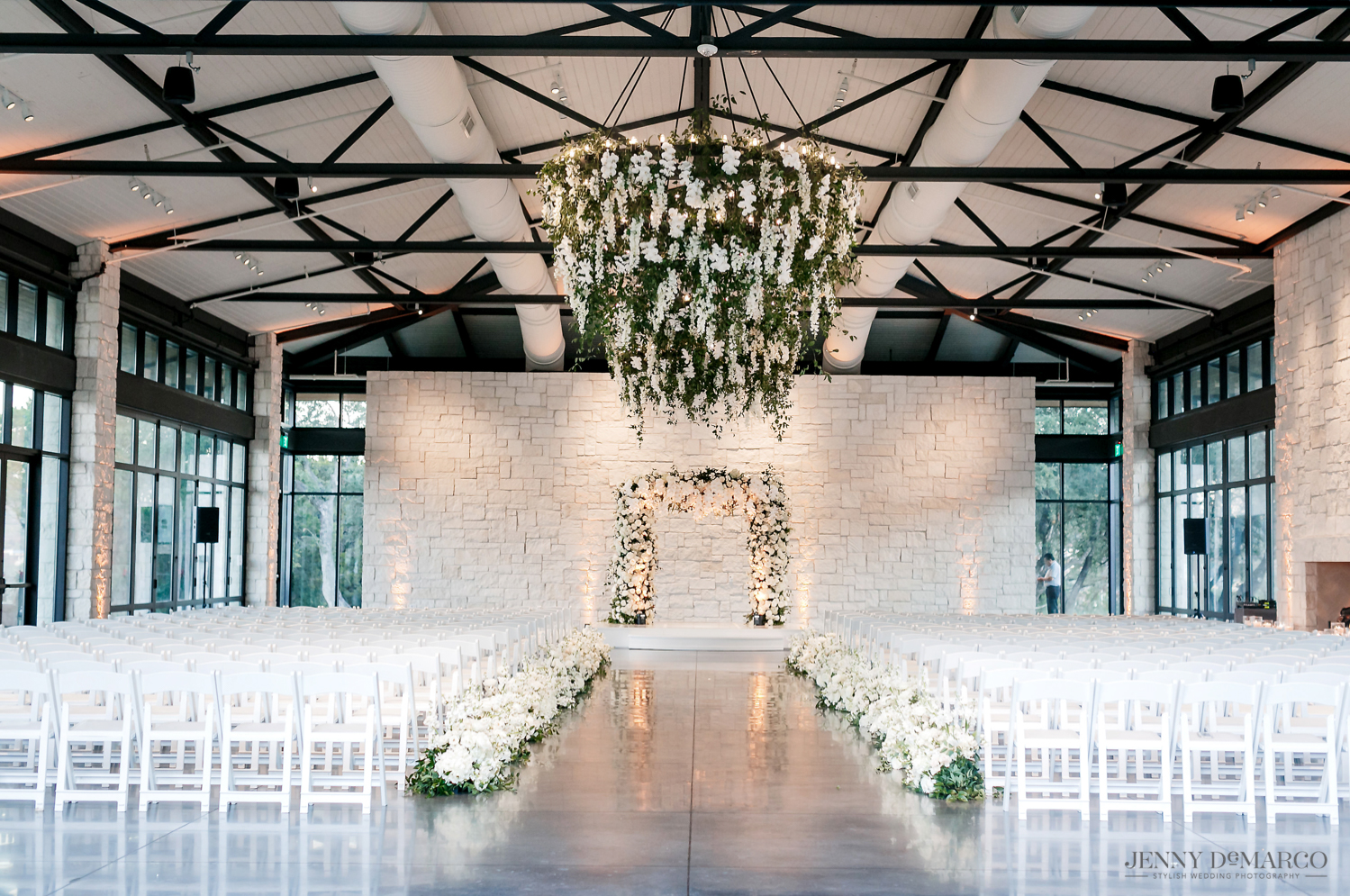 wedding ceremony with white flower and greenery alter and chandelier
