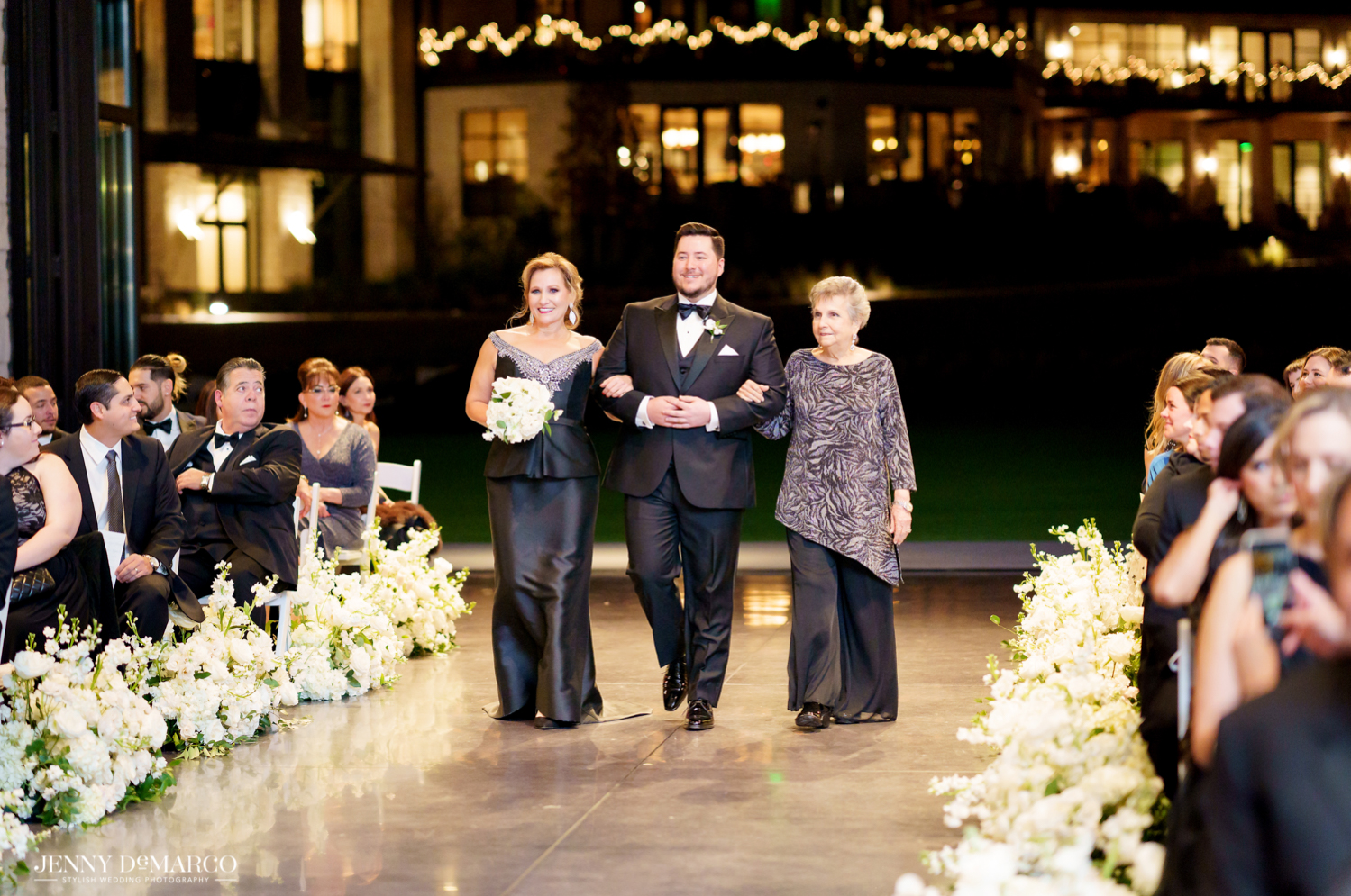the groom walking his mother and grandmother down the aisle
