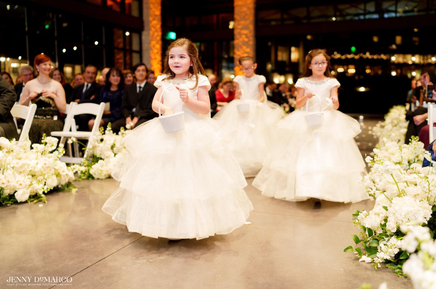 the flower girls walking down the aisle in white dresses