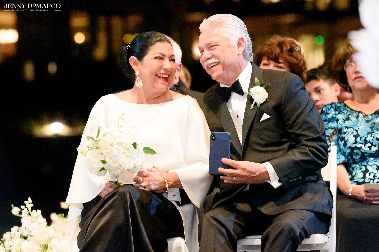 the father and mother of the bride smiling while the father of the bride snaps a photo with his phone