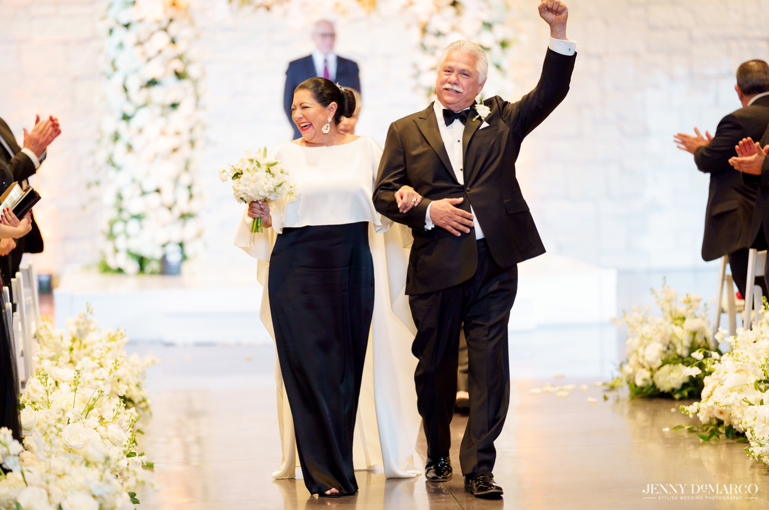 father and other of the bride walking down the aisle and celebrating