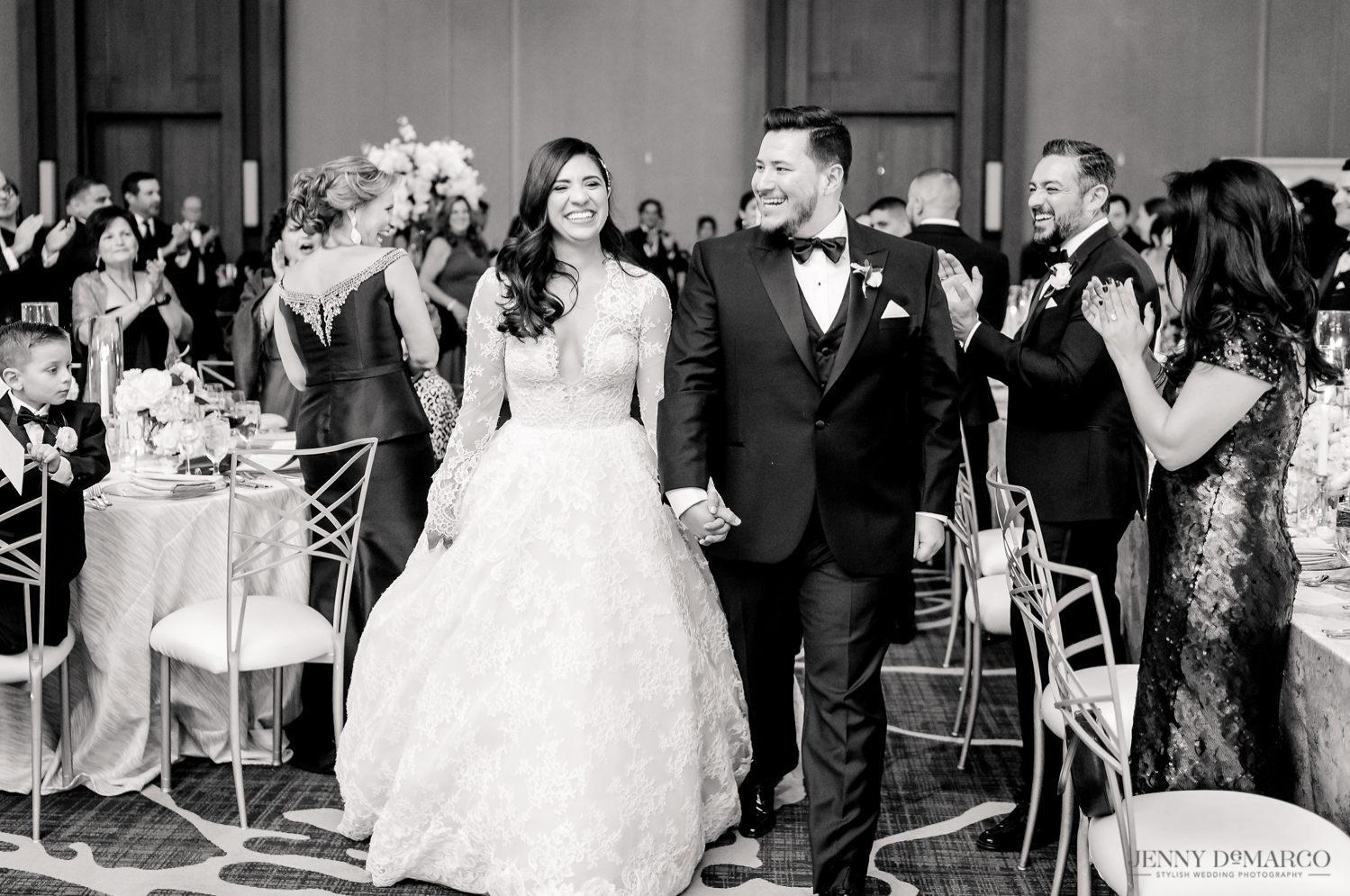 bride and groom walking into the reception smiling as all the guests clap