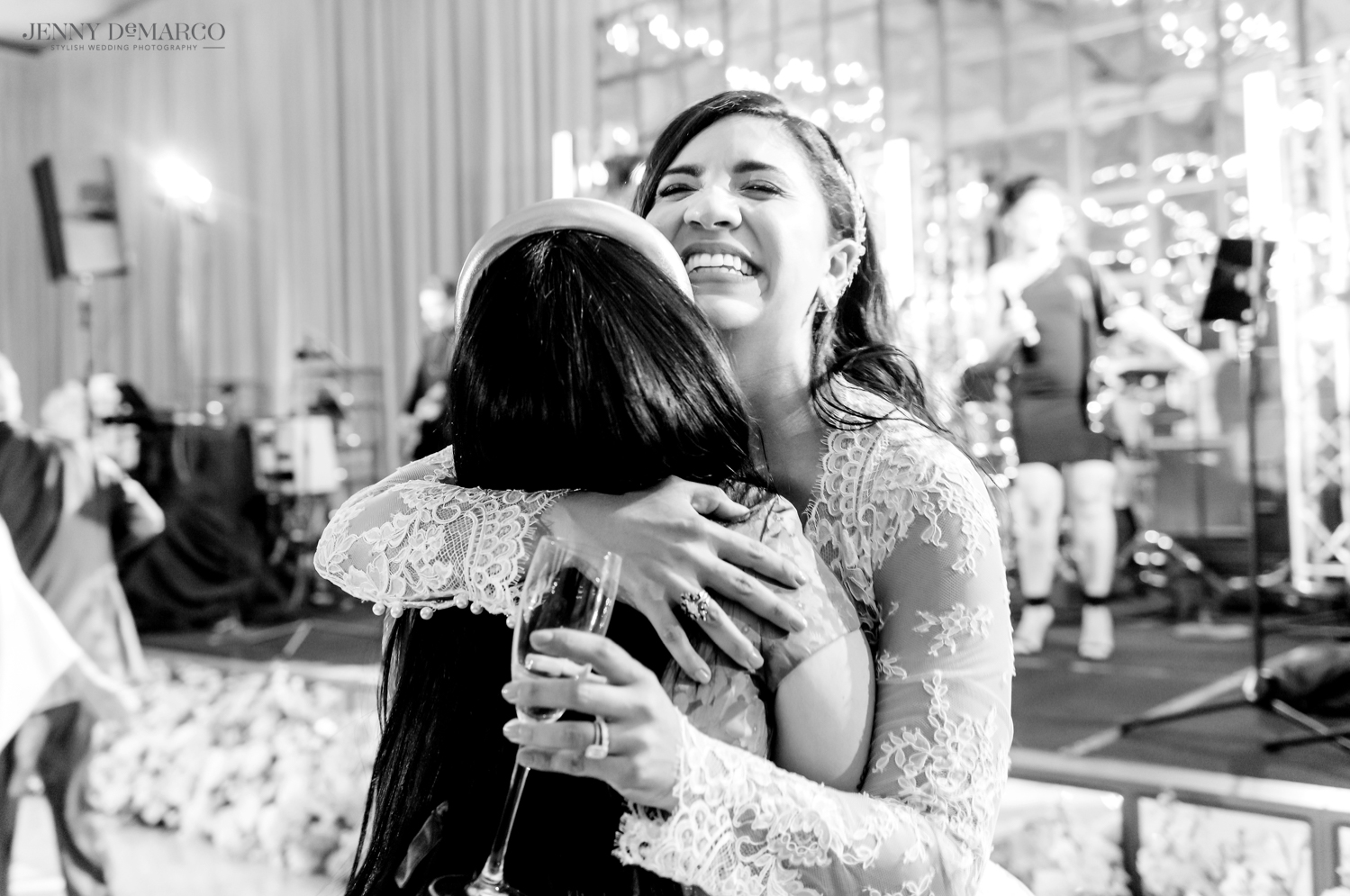 bride smiling as she hugs one of her friends