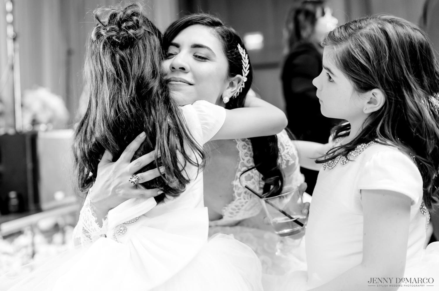 bride hugging the flower girls