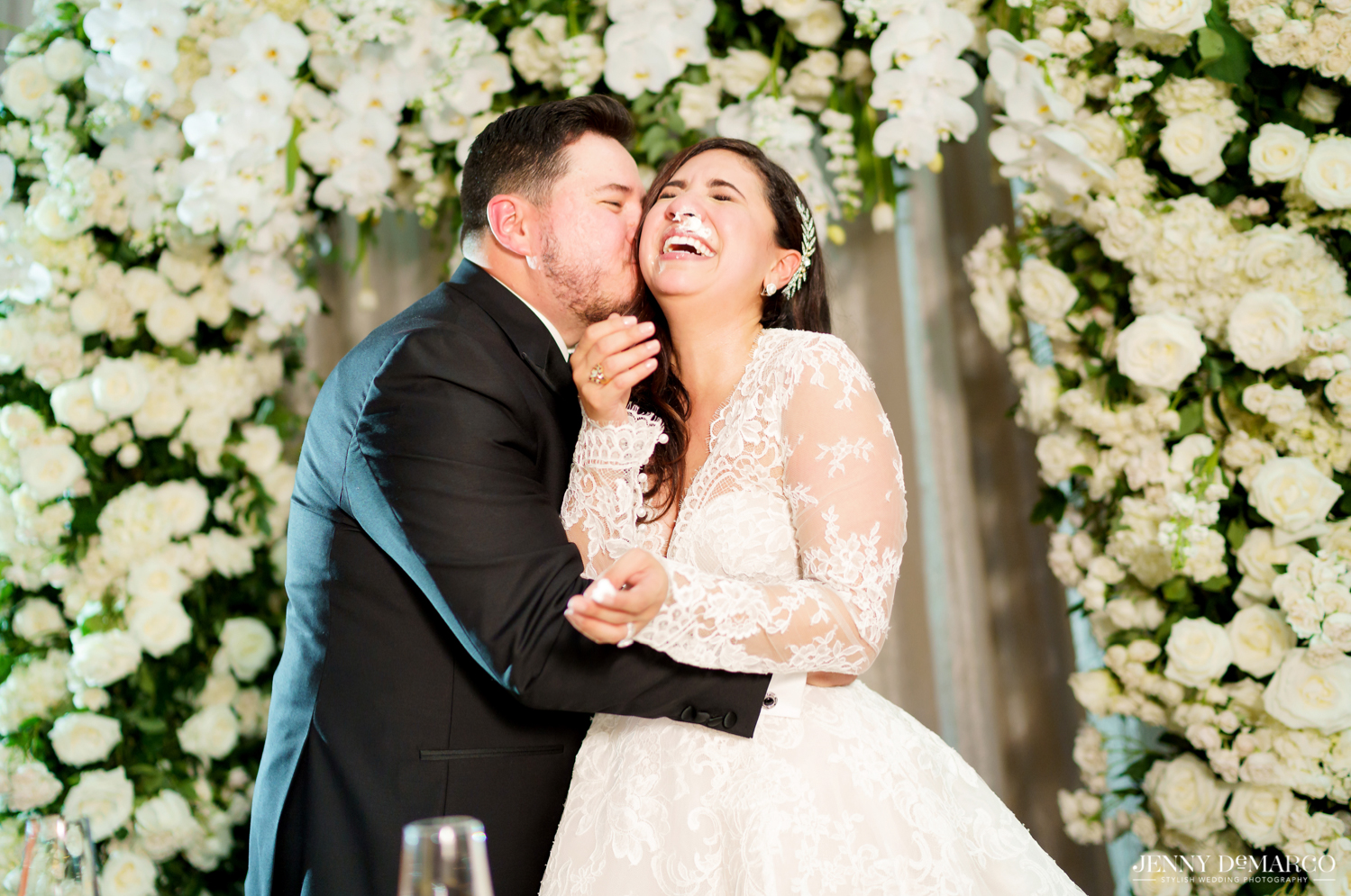 groom shoving cake on the brides face while she laughs