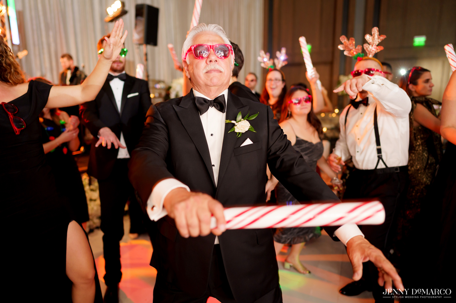 father of the bride dancing at the wedding reception with a candy cane stick and red light sunglasses