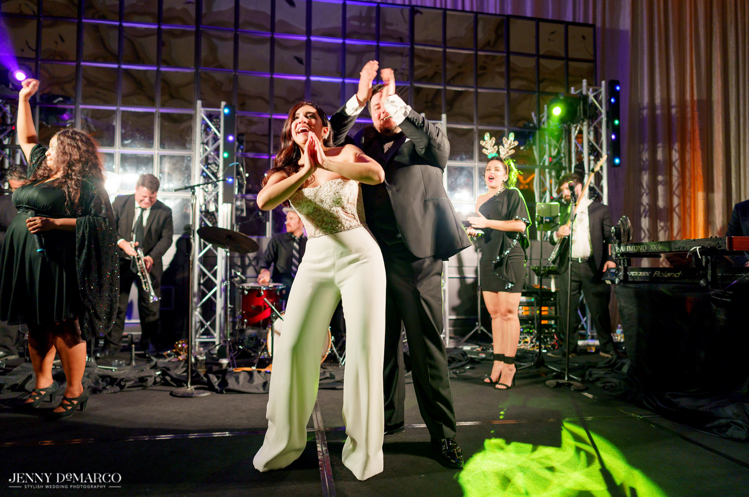 the bride and groom dancing on stage with the band