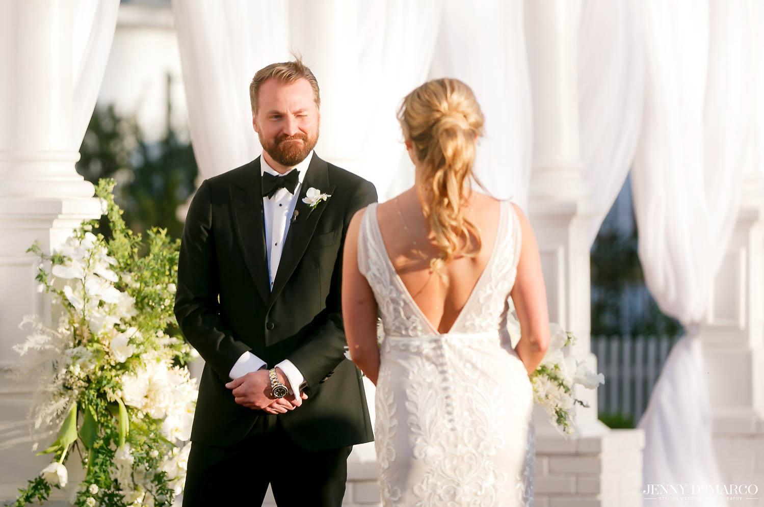 groom winking at bride as she walks up to the center of the ceremony