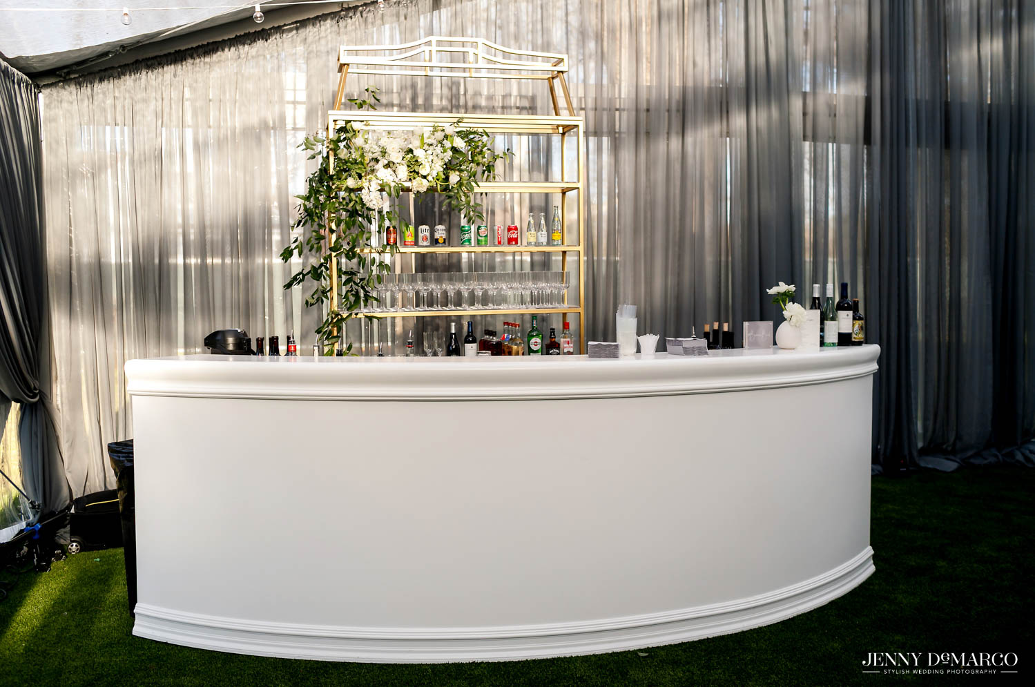 white bar in corner of tent with golden shelf of drinks