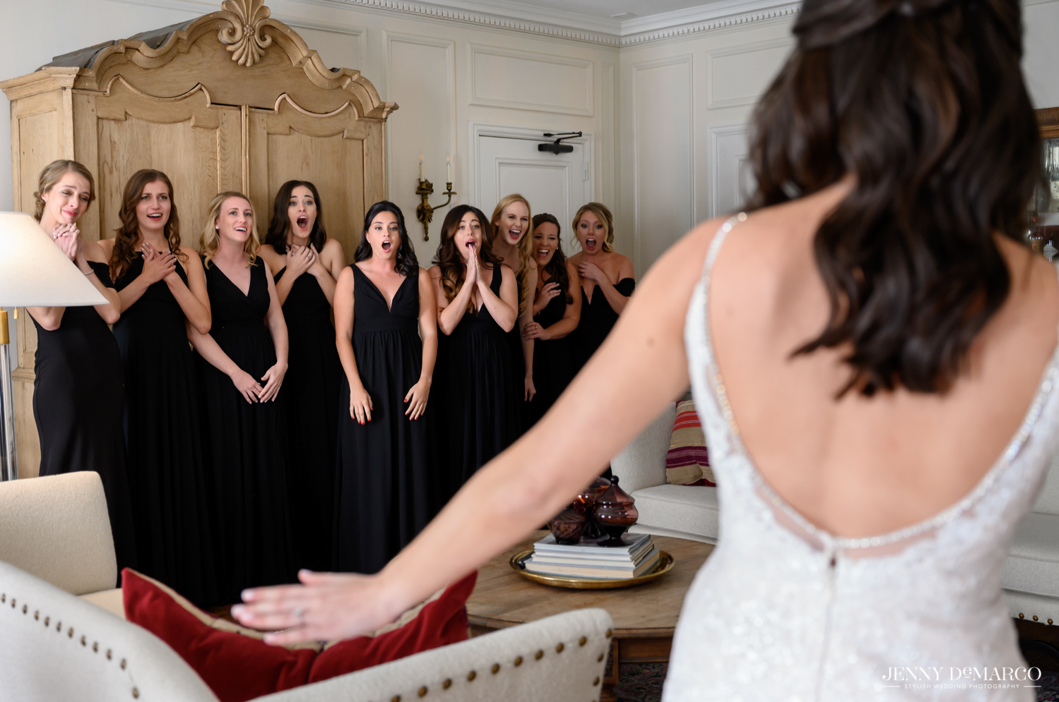 bridesmaids gasping as they see the bride in her dress for the first time