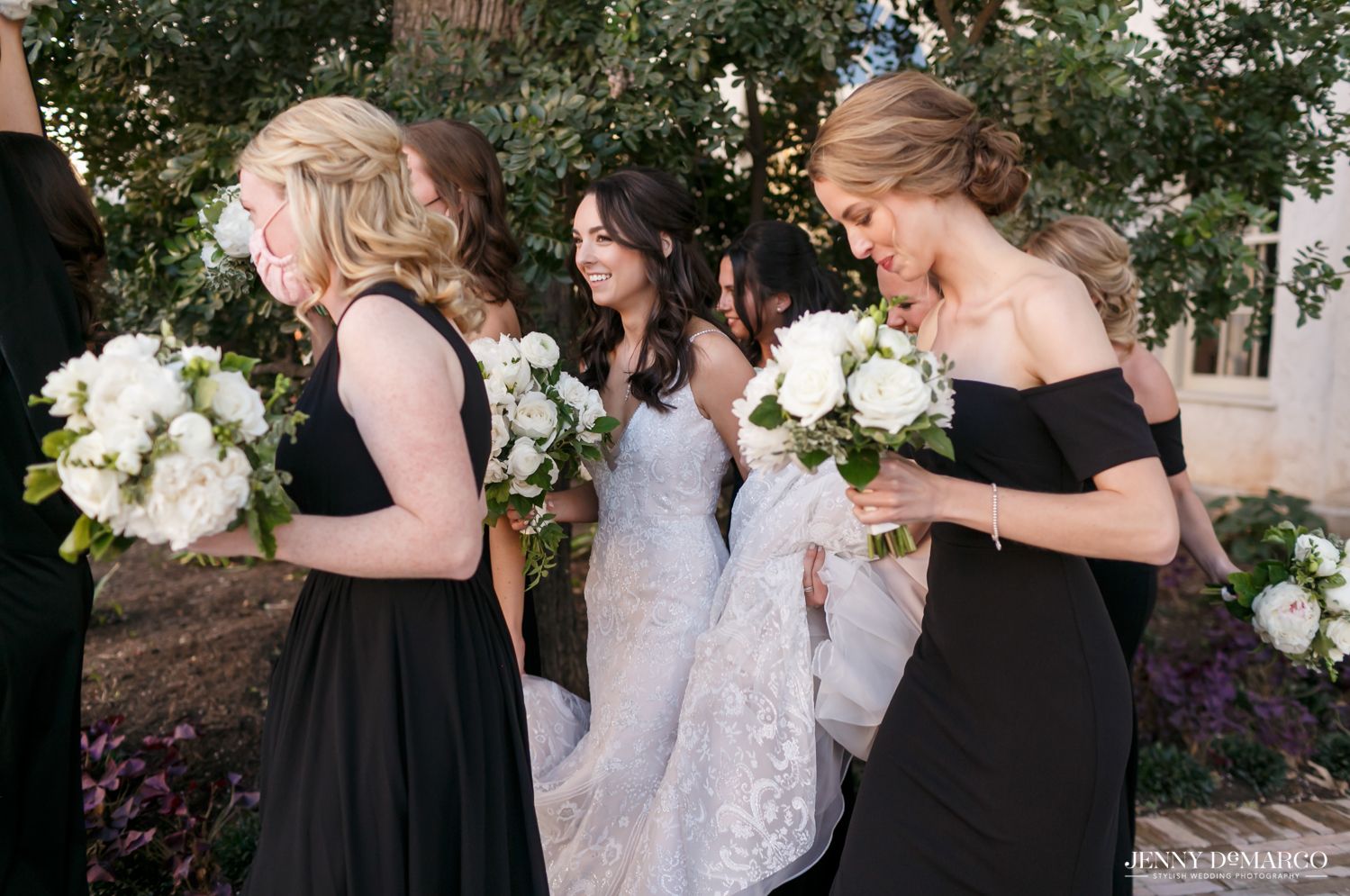 bridesmaids walking with the bride and hold the train of her dress