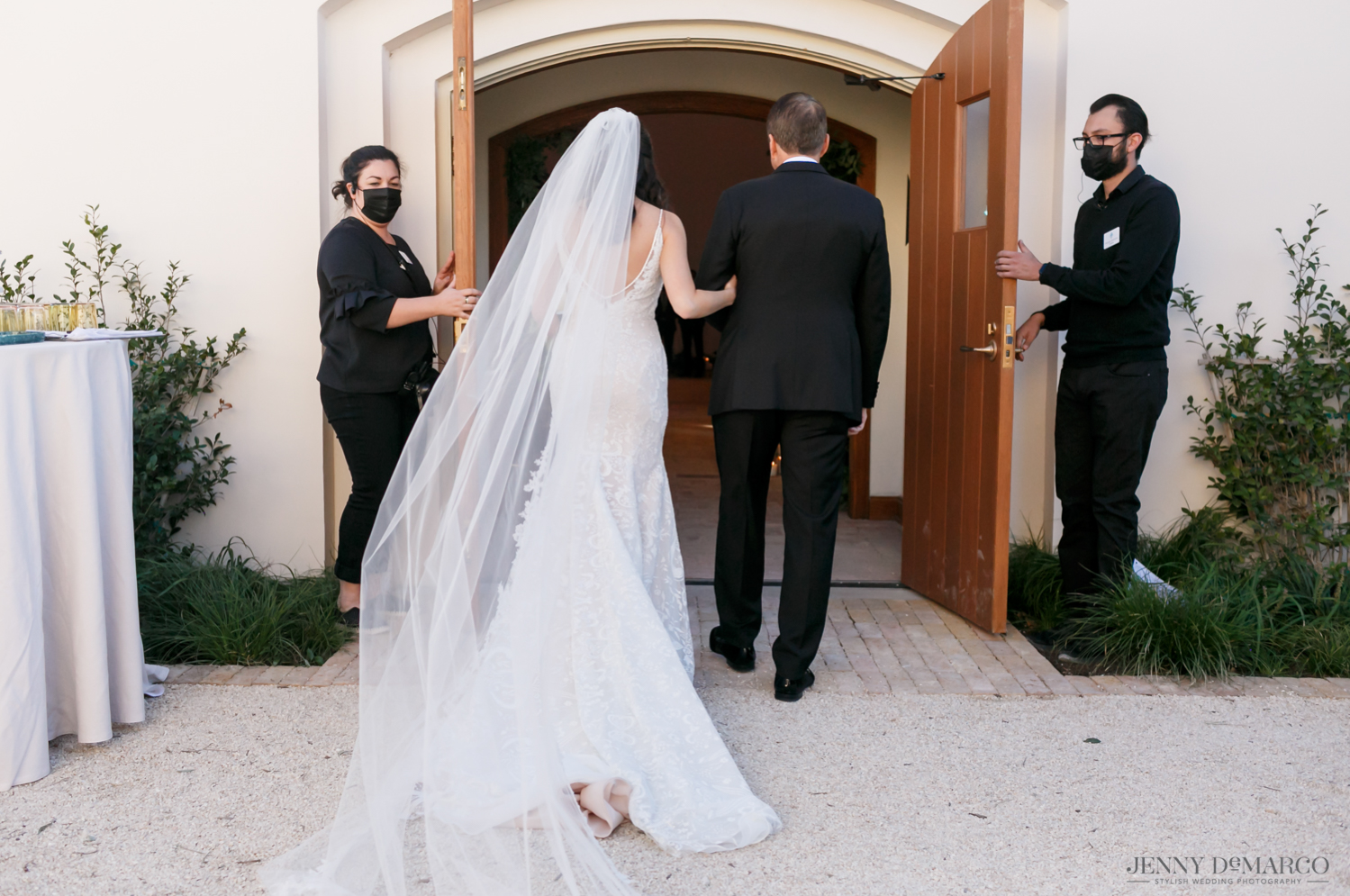 father of the bride walking his daughter into her wedding ceremony as her veil flows behind her