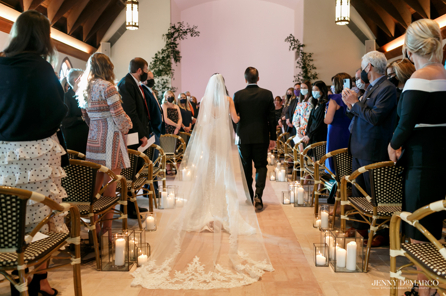 father of the bride walking his daughter down the aisle as her lace veil flows behind her