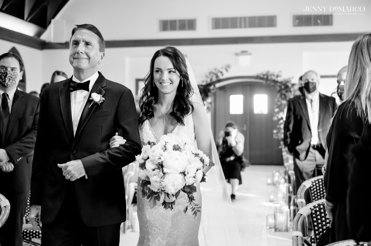 father of the bride smiling as he walks his smiling daughter down the aisle