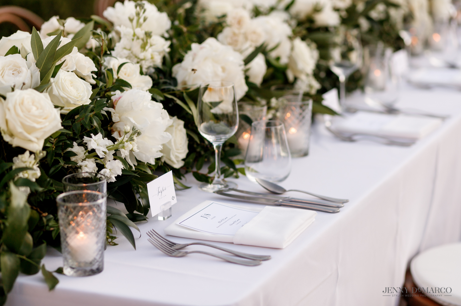 white floral table centerpieces and elegant silver table settings
