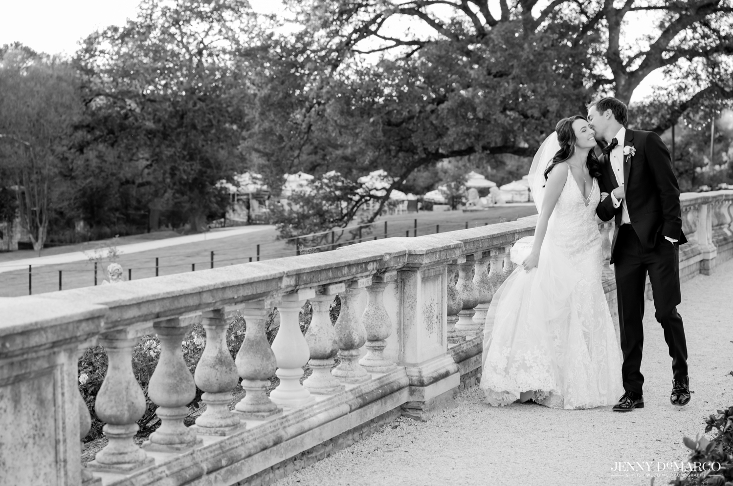 groom kissing bride on the cheek as they walk around the estate at Commodore Perry