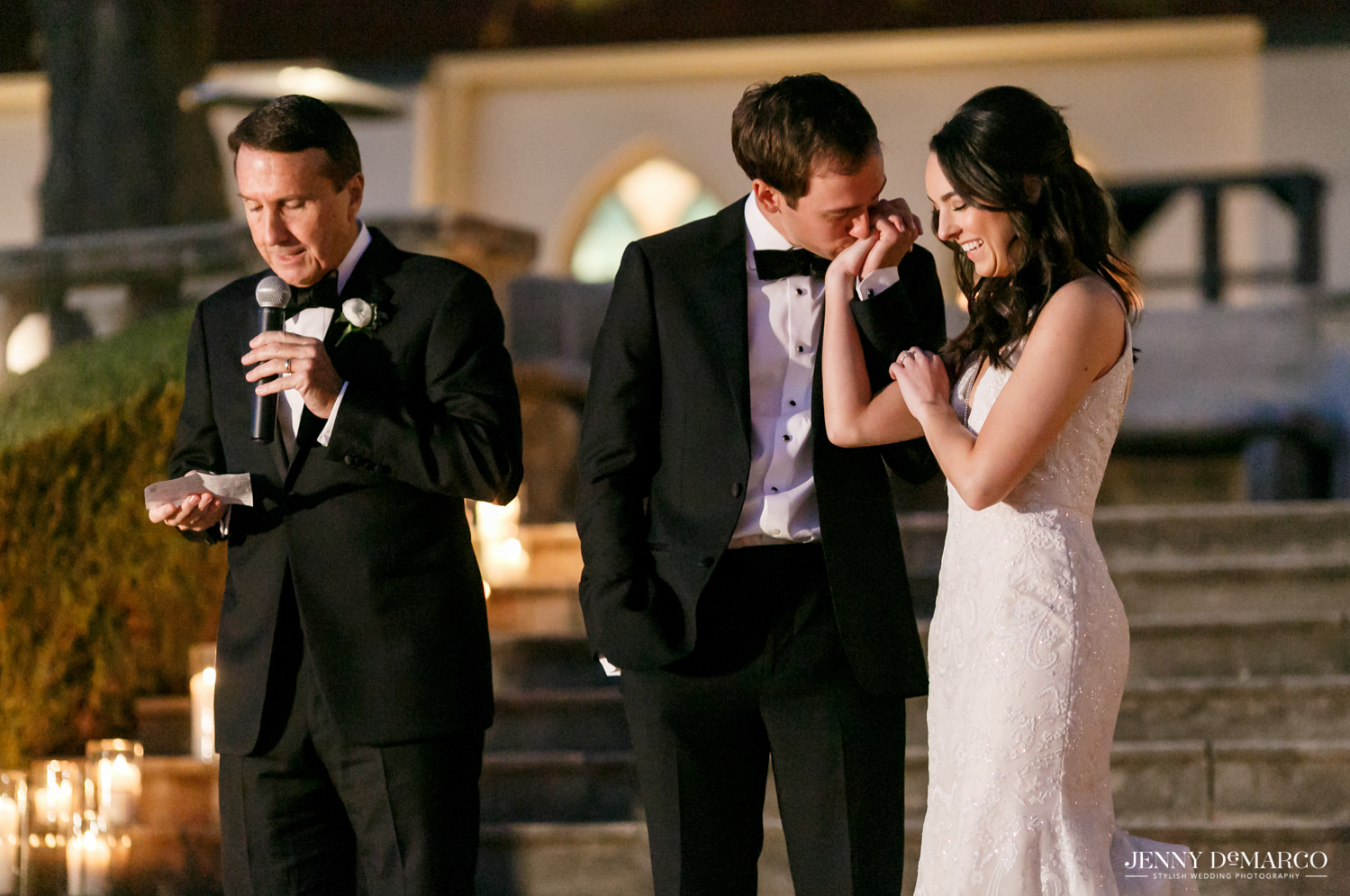 Groom kissing brides hand as the father of the bride gives a toast to the  couple