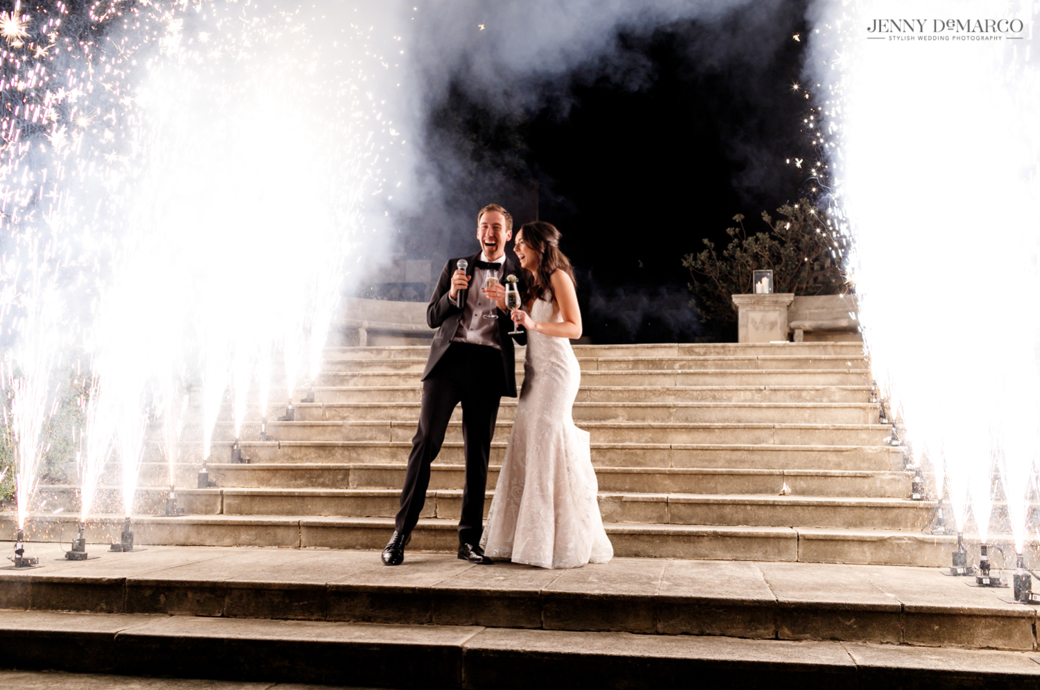 bride and groom laughing as giant sparklers go off around them