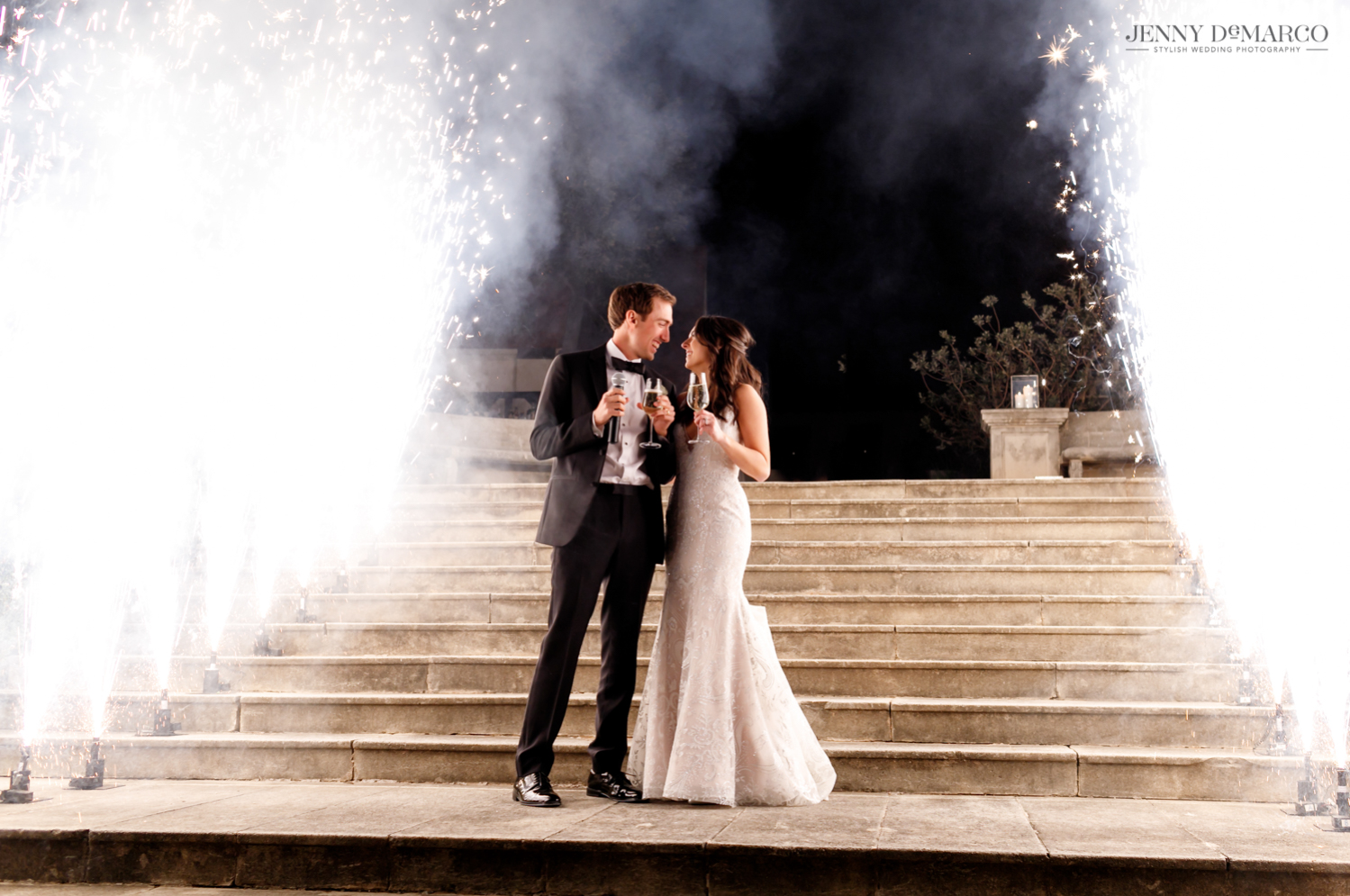 bride and groom looking at each other as giant sparklers go off around them