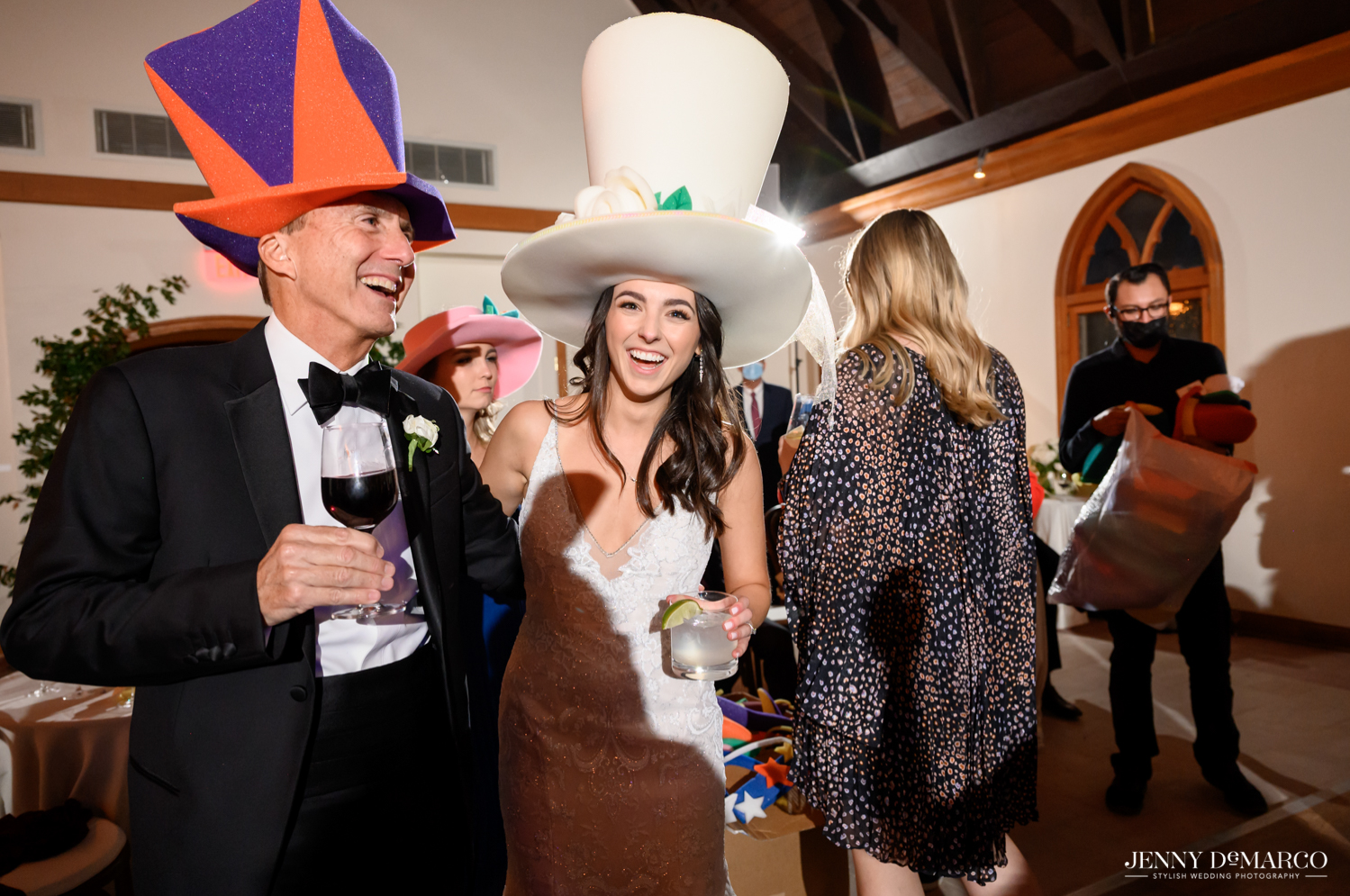 bride and her father dancing with foam party hats on head and drinks in hand