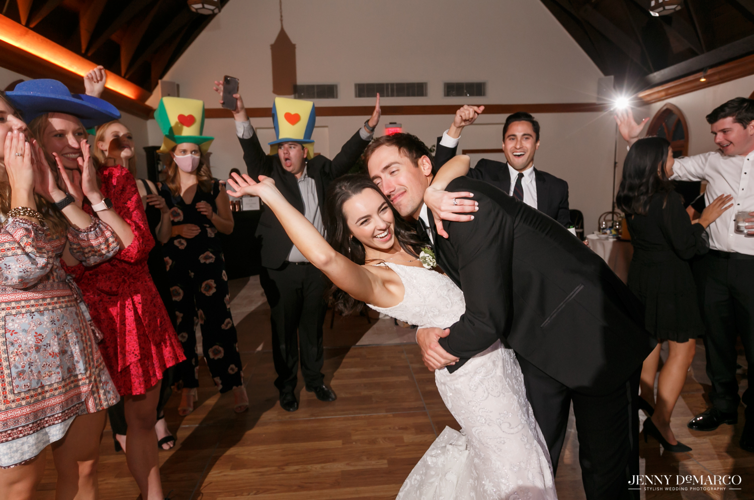 groom dipping his bride as she throw her hands up in celebration
