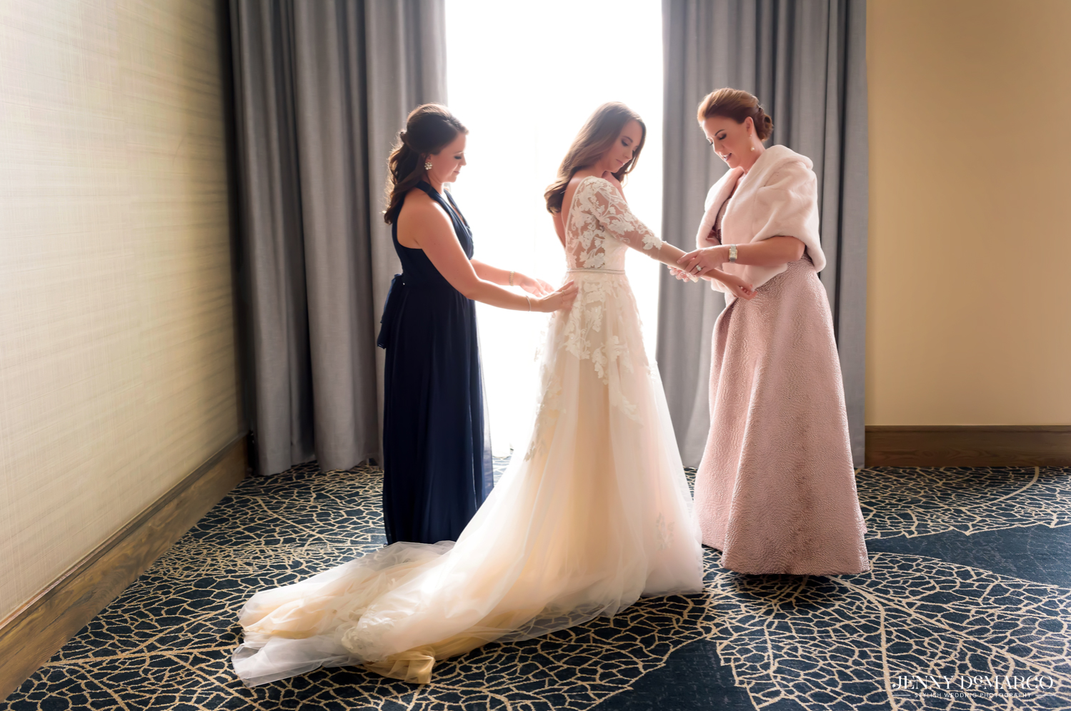 Mother and sister of bride assist with wedding dress