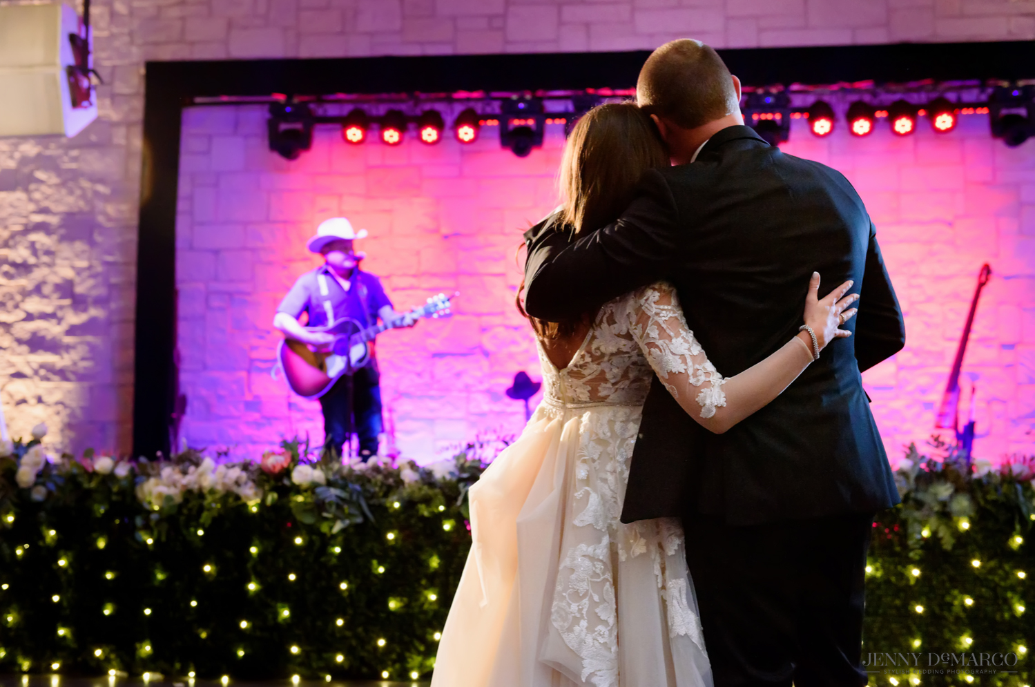 Bride and groom hug while watching surprise wedding singer