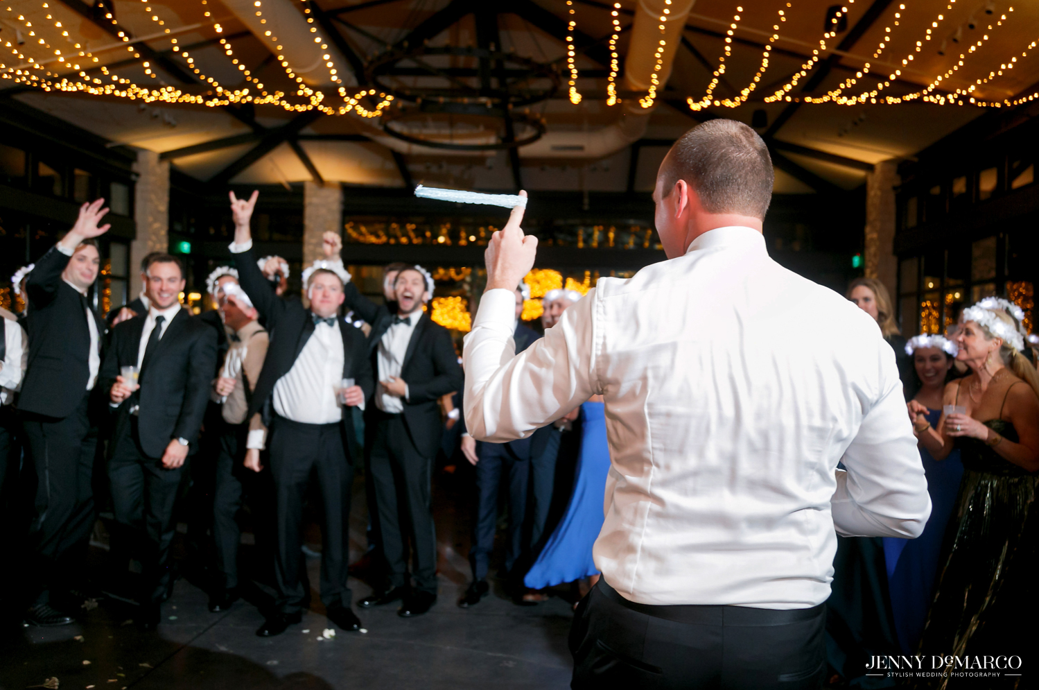 Groom throws brides garter to single groomsmen