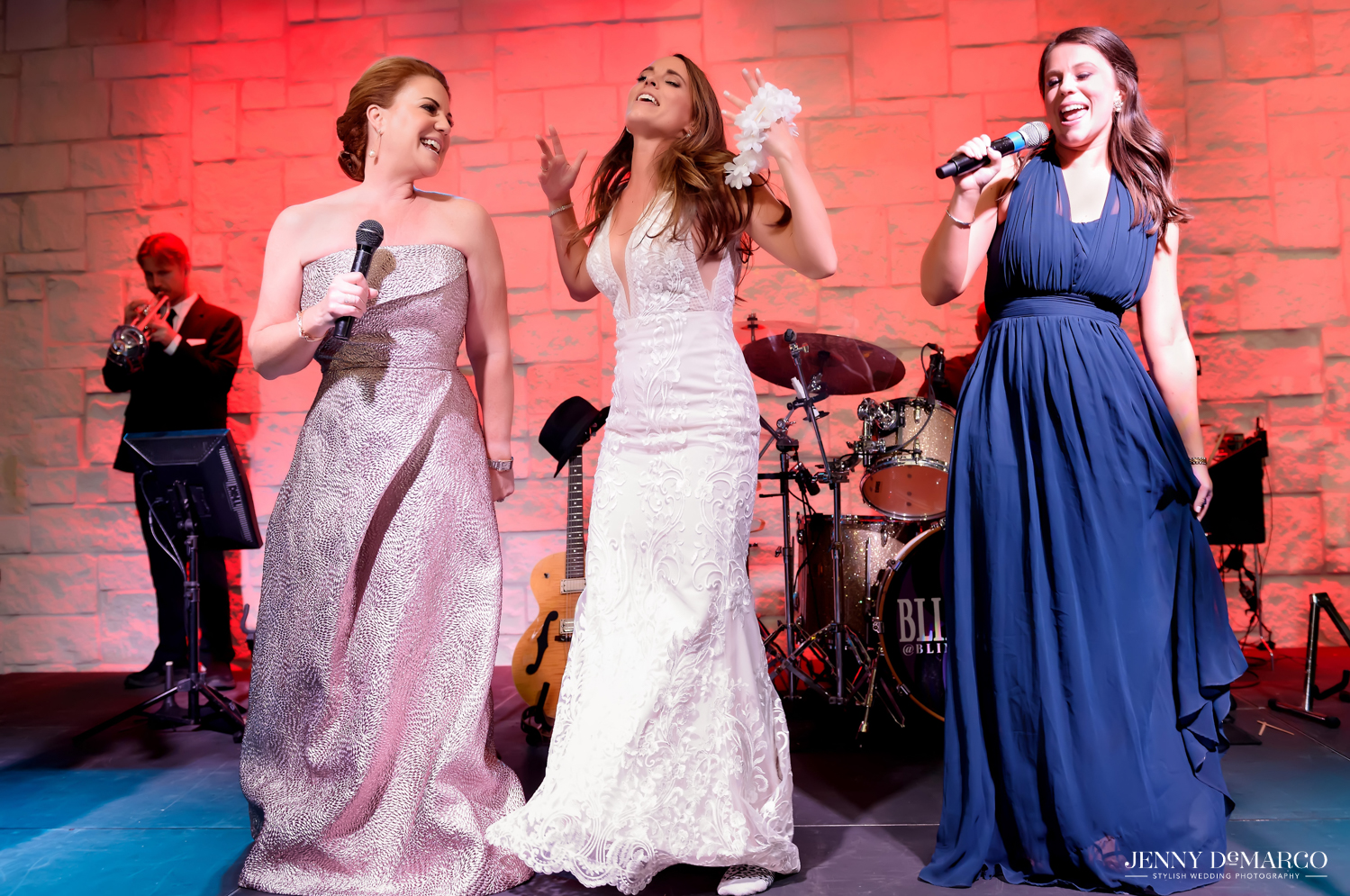 Mother of bride, Bride and sister of bride sing karaoke at wedding reception