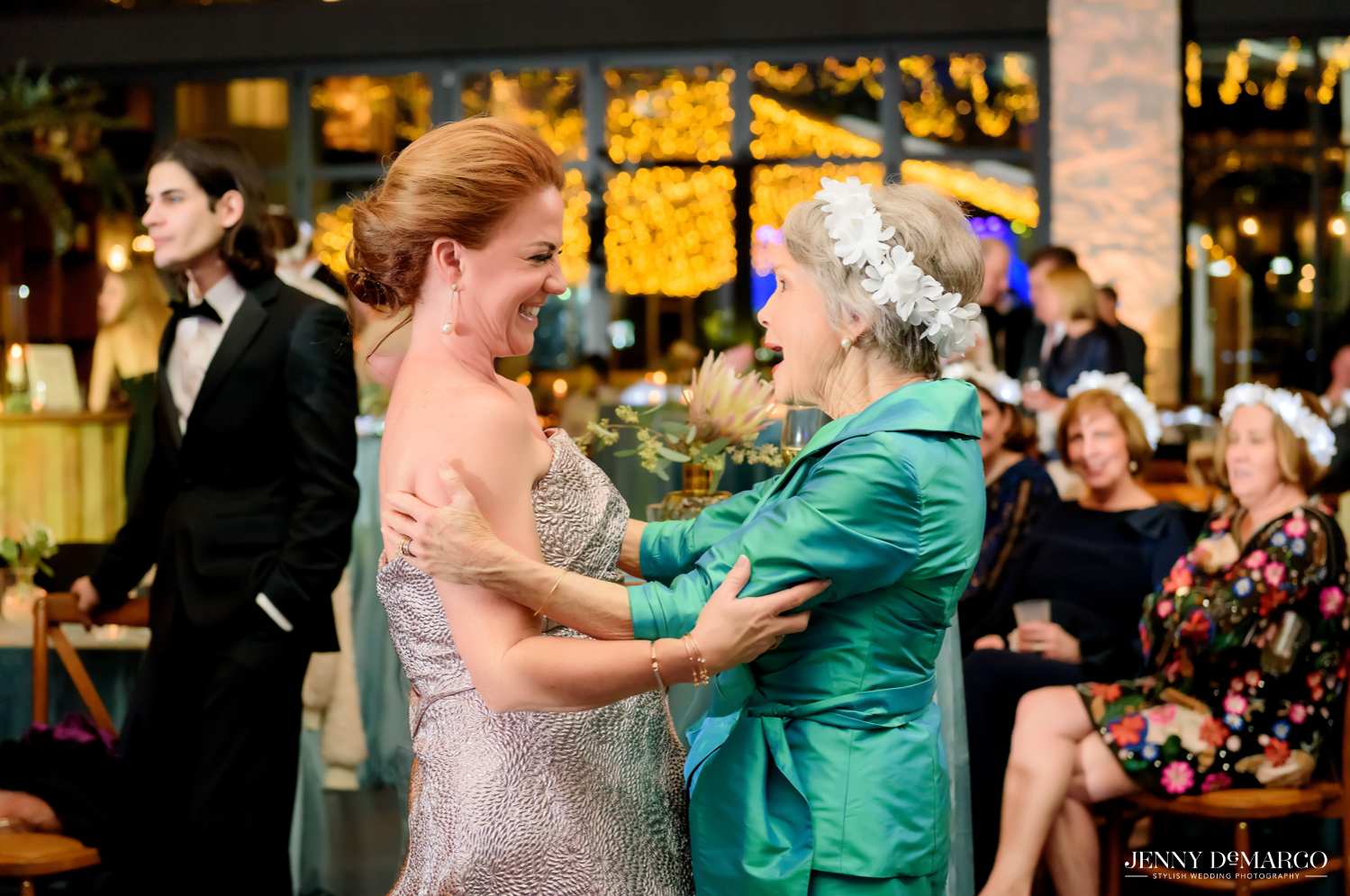 Mother of bride and grandmother hug at wedding reception
