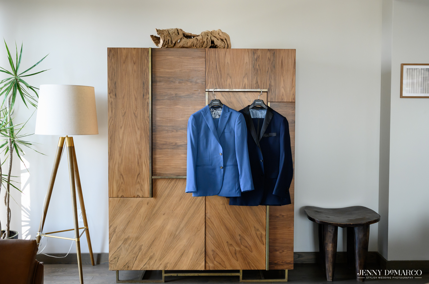 Grooms' suit jackets hanging on wooden armoire