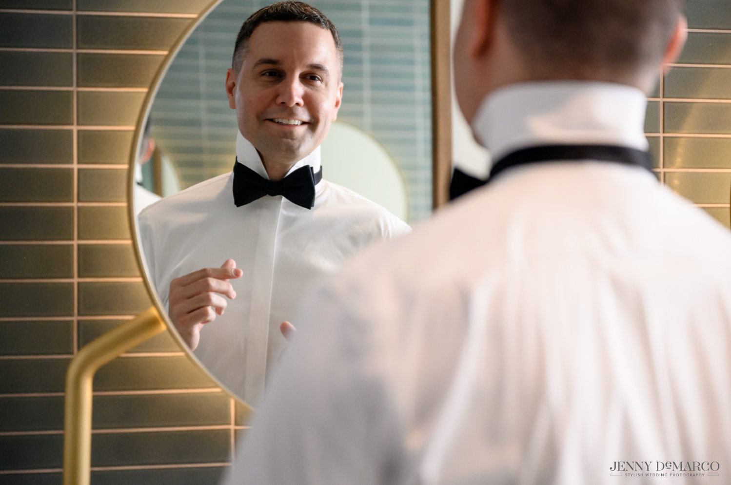 Groom getting ready while smiling into mirror