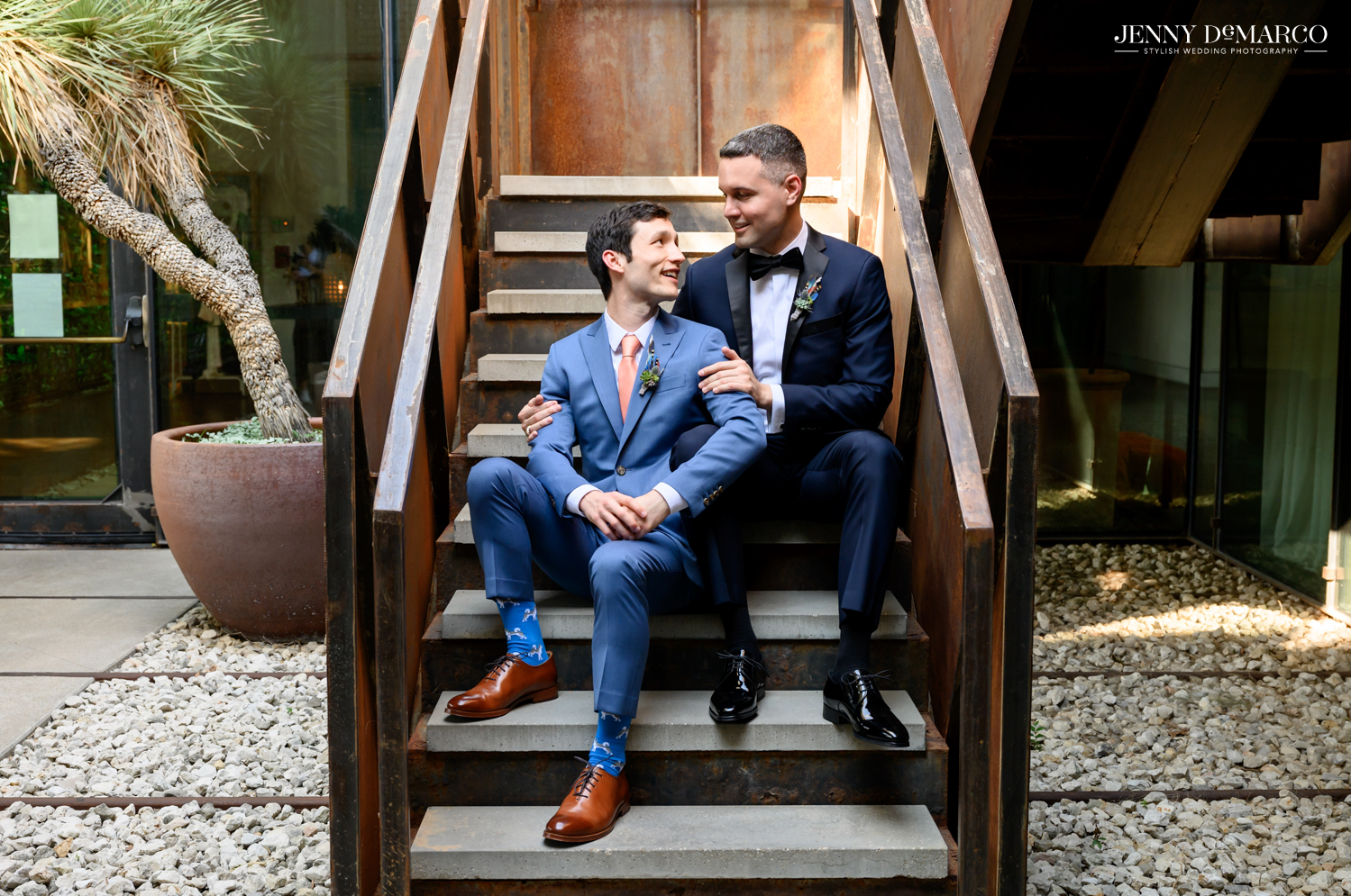 Grooms sitting on stairs and looking at each other
